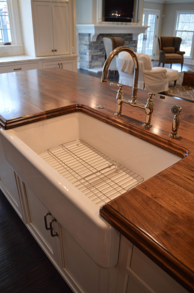 Distressed Walnut Countertop with a sink designed by Studio 76 Kitchens & Baths