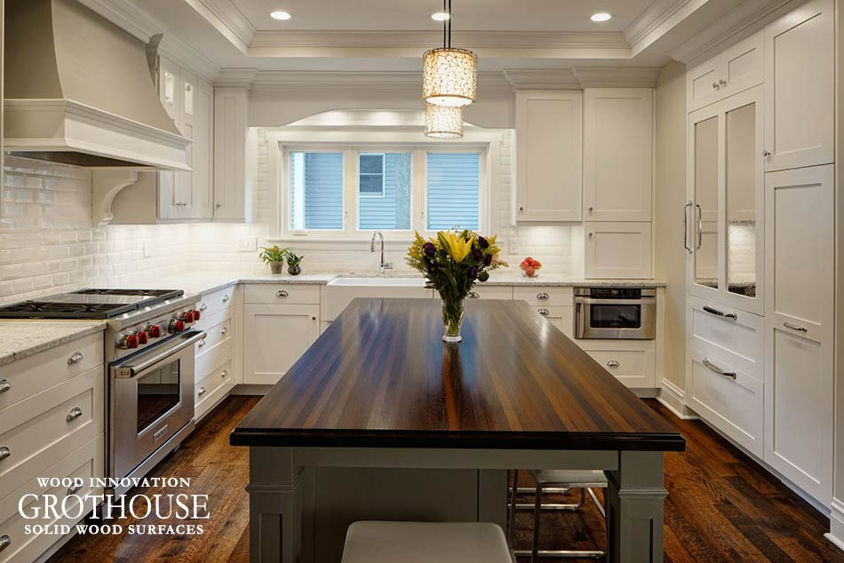 Dark Wood Kitchen Countertop with gray kitchen island and white perimeter cabinetry