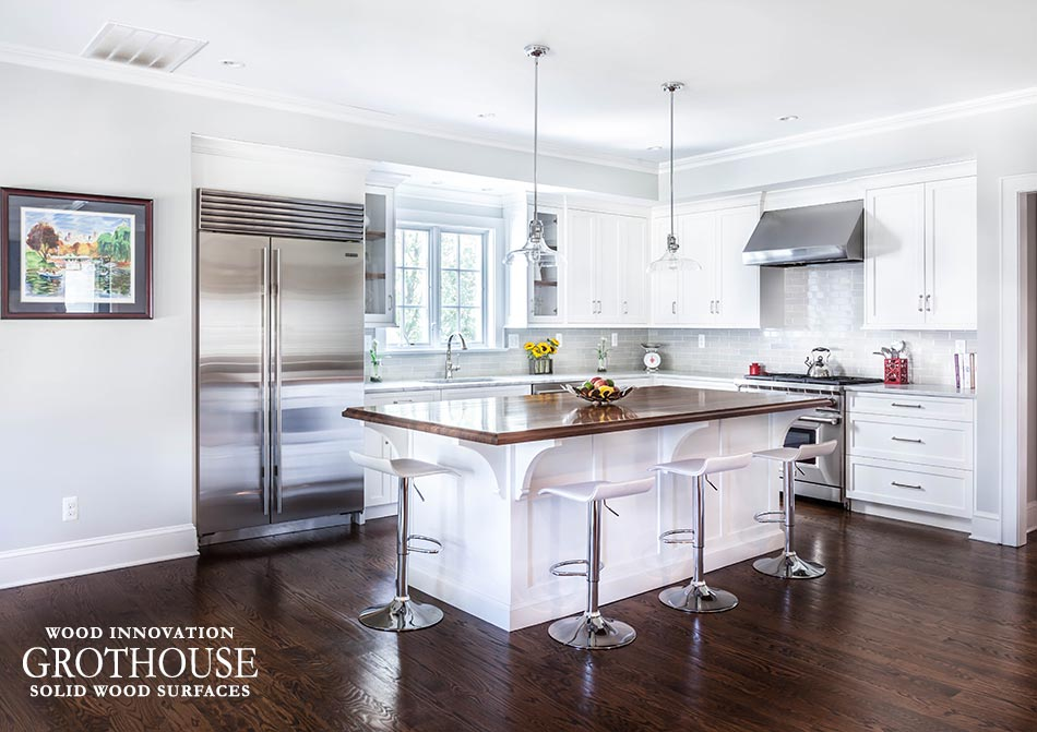 Gray Kitchen Walls walnut wood countertop white cabinets in a design by Stonington Cabinetry & Designs