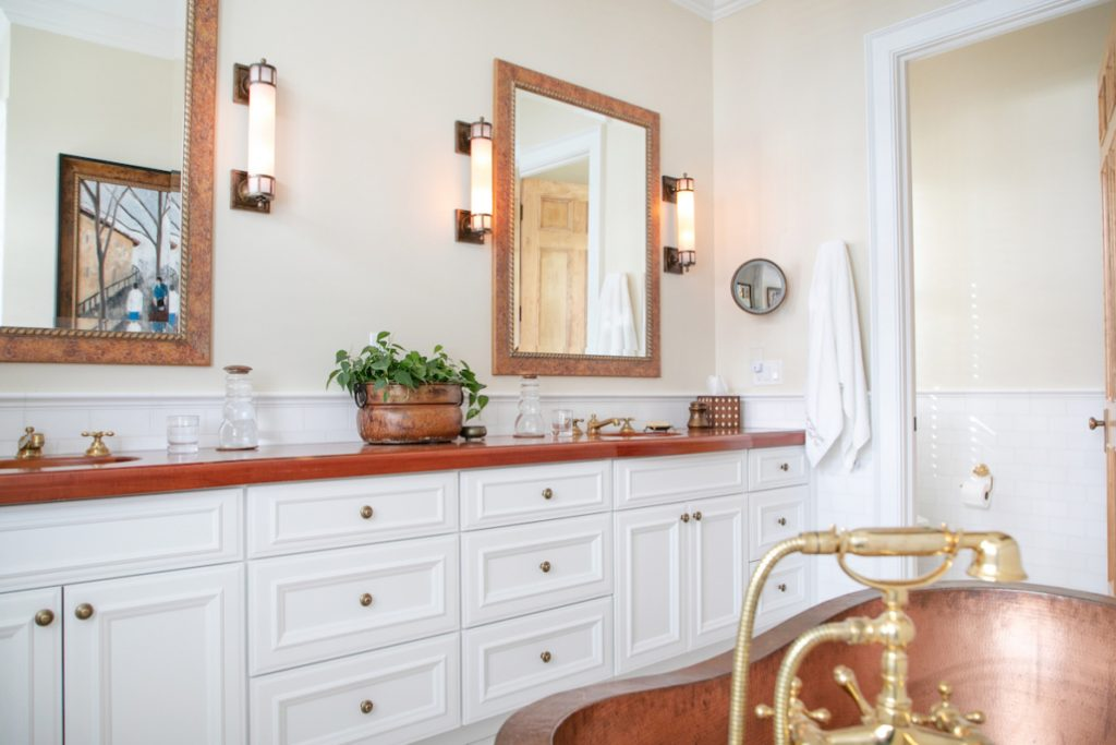 Tigerwood Vanity Top with two undermount sinks, white cabinets and brass hardware