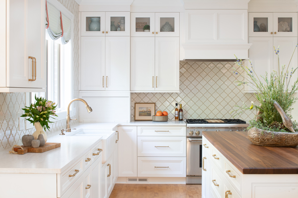 White Kitchen with Honey Bronze Fixtures and a Walnut Island Countertop